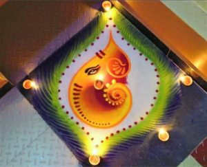 Lord Ganesha Rangoli with lamps on edges